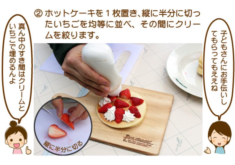 ②ホットケーキを1枚置き、縦に半分に切ったいちごを均等に並べ、その間にクリームを絞ります。