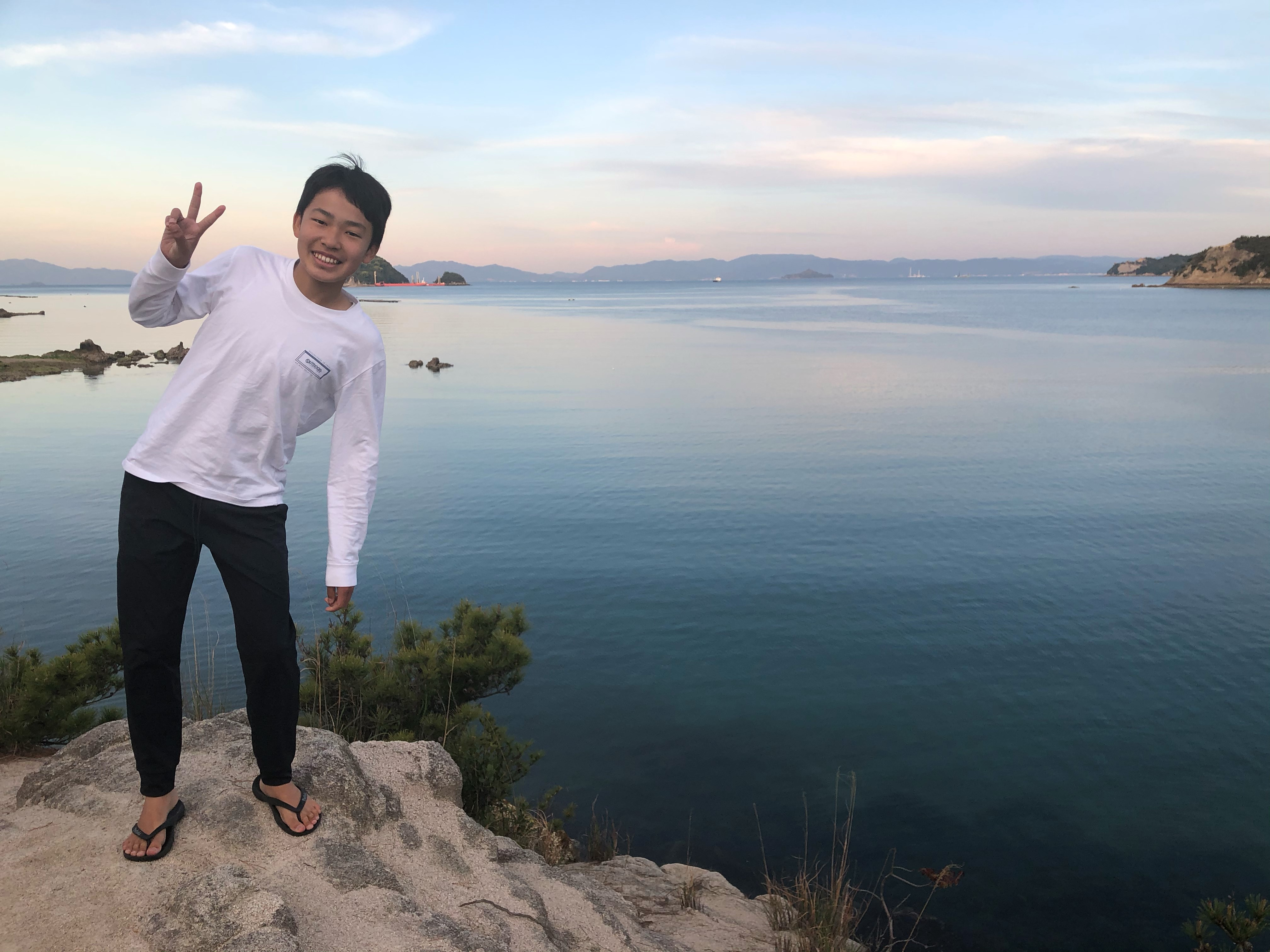 山に登ってピースをしている息子さんの写真