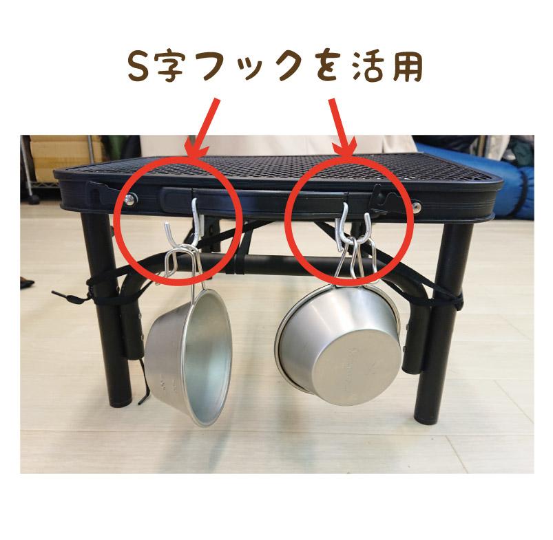 組み立てられたテーブルの横にS字フックでつるされた片手鍋の写真