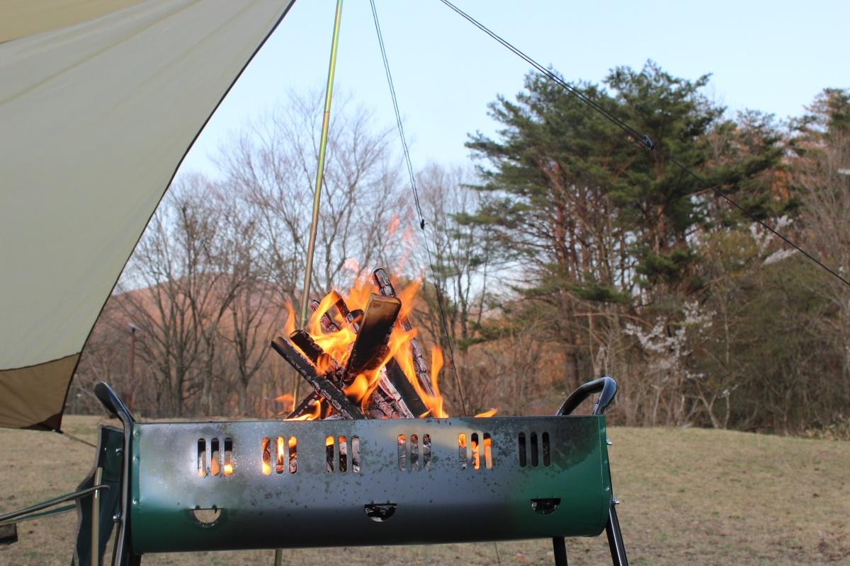 しろくま焚き火タープ」の下で焚き火をしている写真